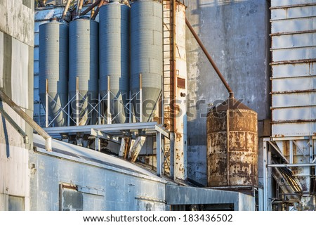 industrial background - exterior of old grain elevator with pipes, ducts, ladders and chutes - stock photo