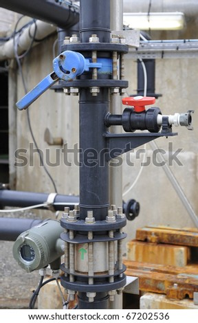 Industrial black plastic tube with some floodgates and pumps