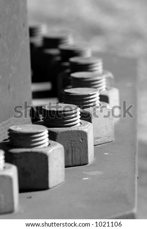 Industrial bolts in a circular row (black and white, shallow focus).