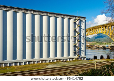 Industrial Building over empty railways and nice yellow bridge across the inlet in Vancouver, Canada. - stock photo