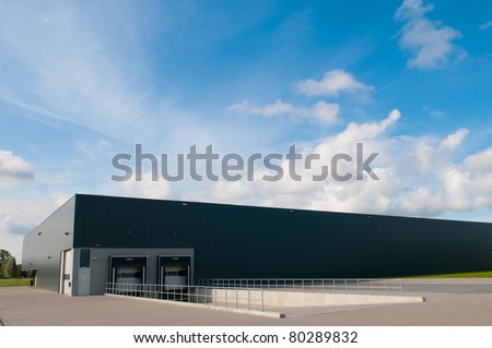industrial building with loading docks and blue sky - stock photo