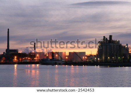 Industrial buildings and ship unloading cargo at sunset - stock photo
