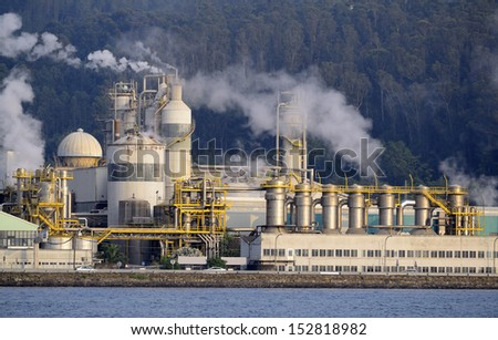 Industrial business in front of oceanic water. Emissions and environment contamination.  - stock photo