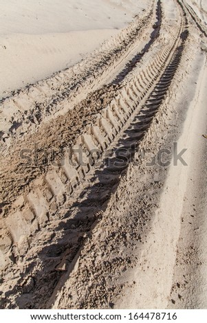 Industrial car tire traces on sand background