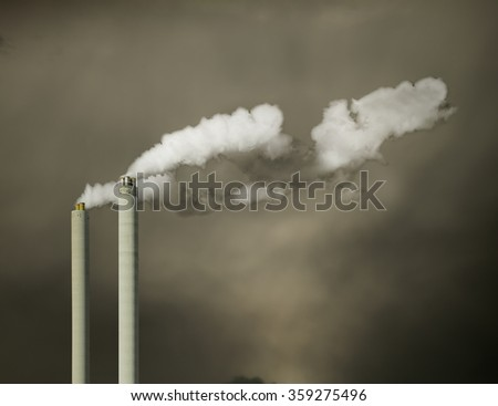 Industrial chimney with white fume and the dark sky - stock photo