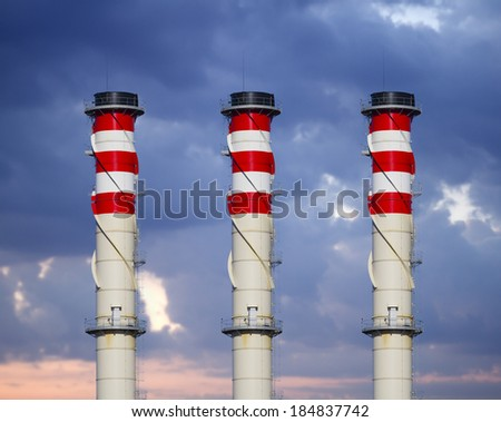 industrial chimneys on cloudy sky at sunset - stock photo