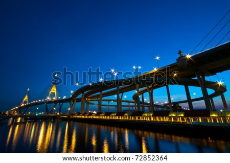 Industrial circle bridge at twilight or night in Bangkok, Thailand.  The name is Bhumibhol bridge 1 and 2. - stock photo