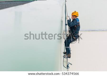 Industrial climber in workwear and helmet looking down from the roof. Professional worker alpinist doing his dangerous job in winter.