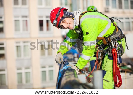 Industrial climber on a roof of a building - stock photo