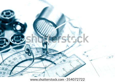 Industrial concept. Few ball bearings near ruler and spectacles on graph paper background - stock photo