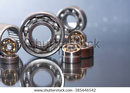 Industrial concept. Few ball bearings on glass surface with reflection - stock photo