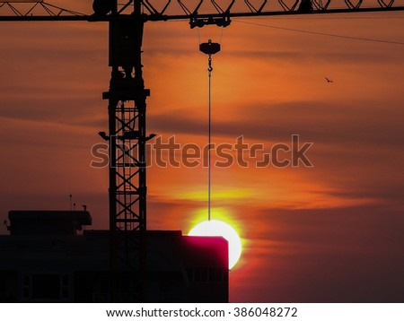 Industrial construction cranes and building silhouettes over hang sun at sunrise. - stock photo