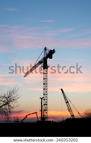 Industrial construction site at sunset with silhouette of a crane.