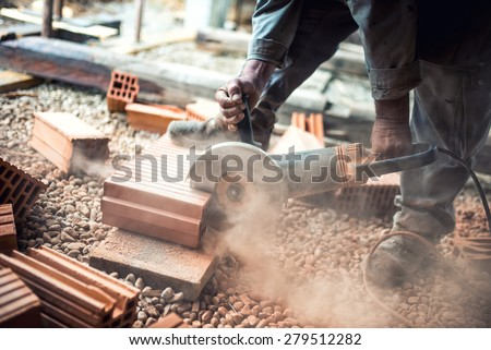 Industrial construction worker using a professional angle grinder for cutting bricks and building interior walls - stock photo