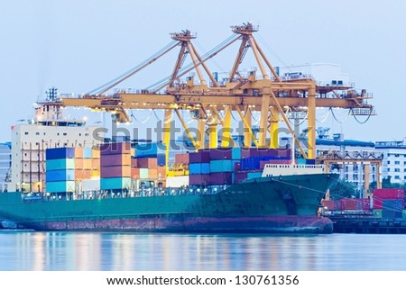 Industrial Container Cargo freight ship with working crane. - stock photo