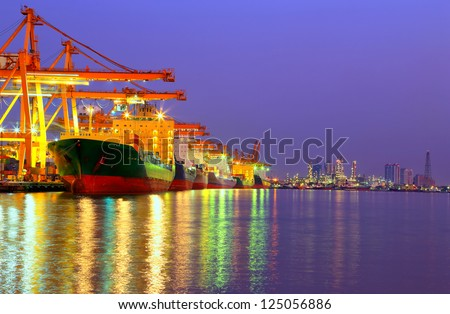 Industrial Container Cargo freight ship with working crane bridge in shipyard at dusk for Logistic Import Export with oil plant background - stock photo