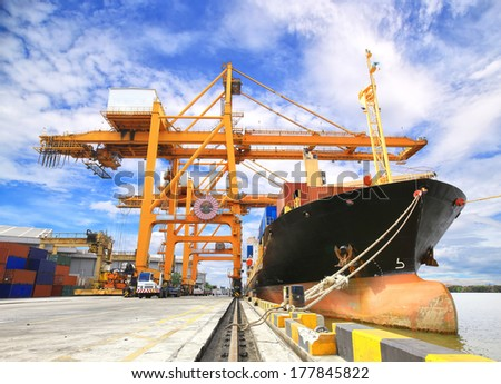 Industrial Container Cargo freight ship with working crane bridge in shipyard with forklif - stock photo