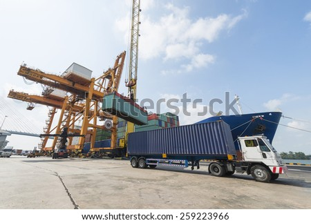 Industrial Container Cargo freight ship with working crane bridge in shipyard with truck. - stock photo