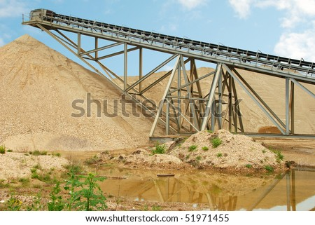 Industrial conveyor belt at gravel extraction pit - stock photo