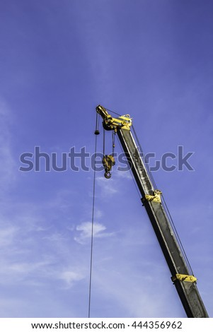 Industrial crane and hook white blue sky background - stock photo