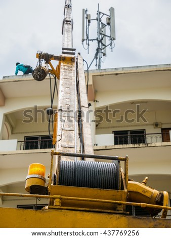 Industrial Crane operating the telecom tower on the building against clouds and sky