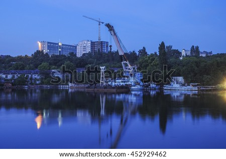 Industrial cranes of reflection in the water. Shipbuilding Plant in Nikolayev, Ukraine - stock photo