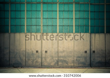 Industrial doors on old airplane hangar  - stock photo