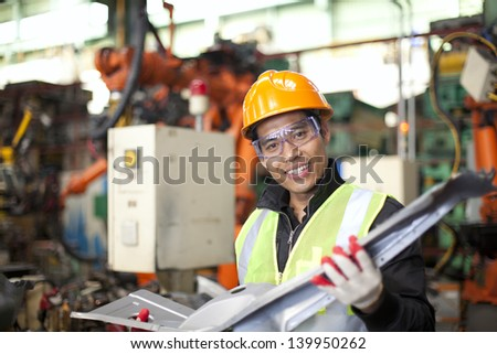 industrial engineer checking quality of metal in factory - stock photo