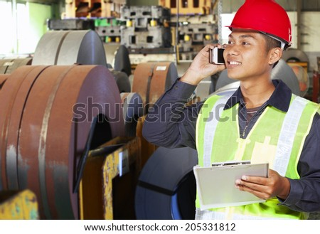 Industrial engineer communication via phone in factory - stock photo