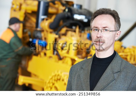 industrial engineer manager with technical drawing at heavy industry machinery assembling on production manufacturing factory line - stock photo