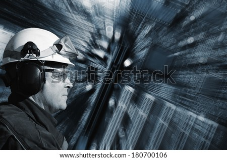 industrial engineer set against a large circuit-board, technology and electronics - stock photo