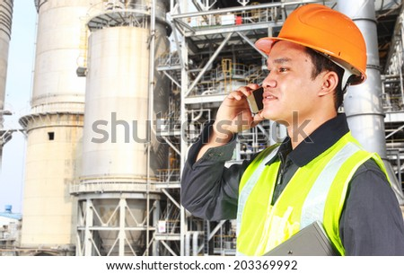 Industrial engineer standing in front of a large oil refinery conversation via phone - stock photo