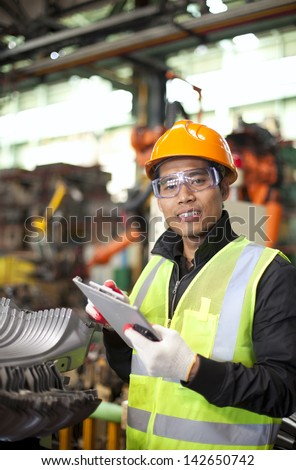 industrial engineer taking notes in factory vertical image - stock photo