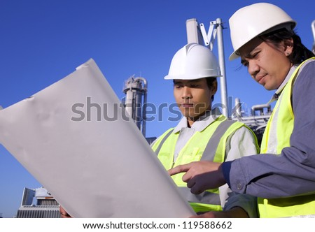 Industrial engineering. Images of two engineer discussion front of large refinery - stock photo