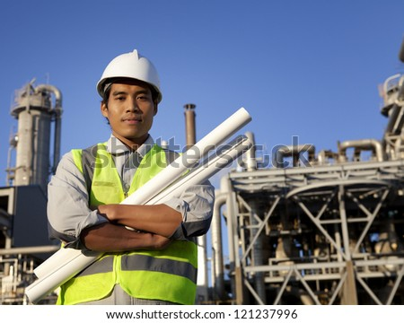 Industrial engineering. Portrait of young asian chemical industrial engineer wearing safety vest and helmet with large oil refinery background and blue sky - stock photo