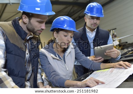 Industrial engineers meeting in mechanical factory - stock photo