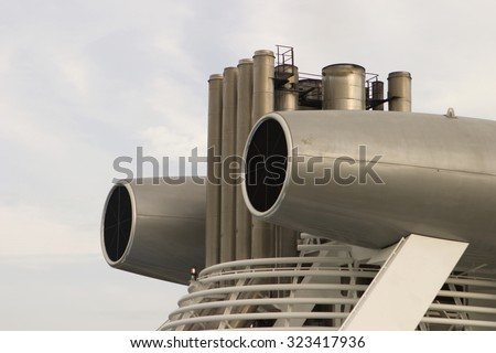 Industrial equipment on the main mast and smokestack of a large cruise ship. They look like jet engines but are probably air blowers and heat exchangers used to provide ventilation. - stock photo