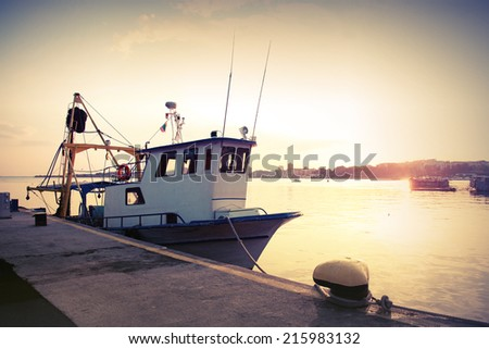 Industrial fishing boat is moored in port. Vintage toned photo - stock photo