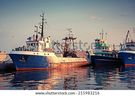 Industrial fishing boats are moored in port. Vintage toned photo - stock photo