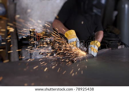 industrial grinding sparks with worker and protective mask and gloves - stock photo