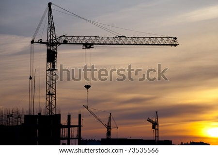 Industrial landscape. Construction cranes and concrete structure at sunset - stock photo