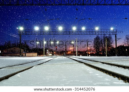 Industrial landscape - illuminated railway station by winter night with snowfall - stock photo