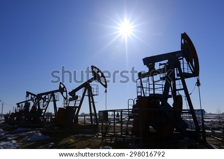 industrial landscape oil pumps in the early spring on a blue sky background