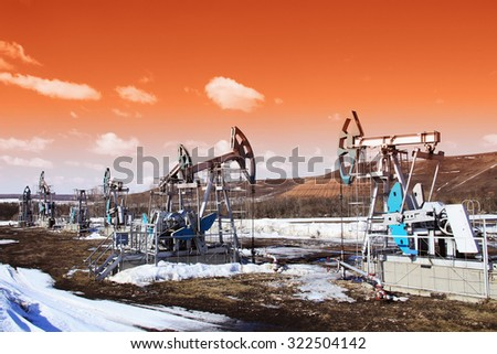 industrial landscape Oil pumps in the field on a background of blue sky and white clouds on a sunny day in early spring - stock photo