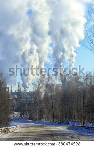 industrial landscape road through the avenue of trees and industrial plant with smoke from the chimneys on the horizon in the winter - stock photo