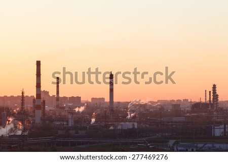 Industrial landscape with oil refinery at sunrise.