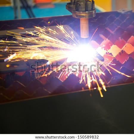 Industrial laser cutter with sparks. - stock photo