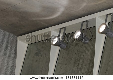 industrial lights on the wall inside a building - stock photo
