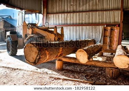industrial log loader operating at industrial wood production factory - stock photo