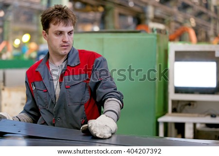 Industrial Man Worker working at CNC forming equipment for processing sheet metal in Factory Workshop - stock photo